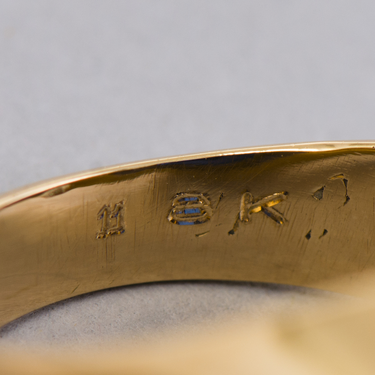 A gold 18K Freemason ring with a synthetic blue sapphire