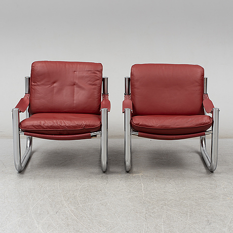 A pair of arne norell easy chairs, chromed steel frame and red leather seats, labeled norell made in sweden,