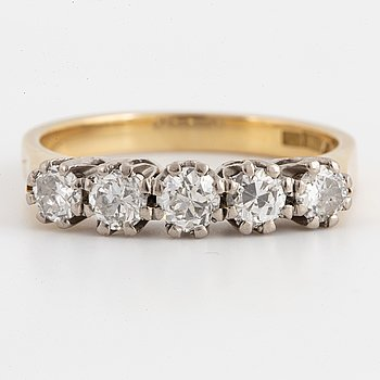 An 18K gold ring set with brilliant-cut diamonds.