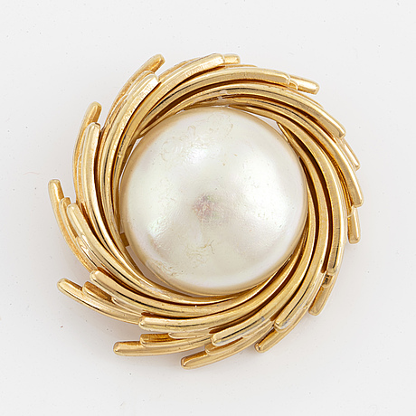 A metal brooch set with an imitation pearl