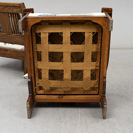 A pair of oak easy chairs in the manner of carl westman, circa 1900.