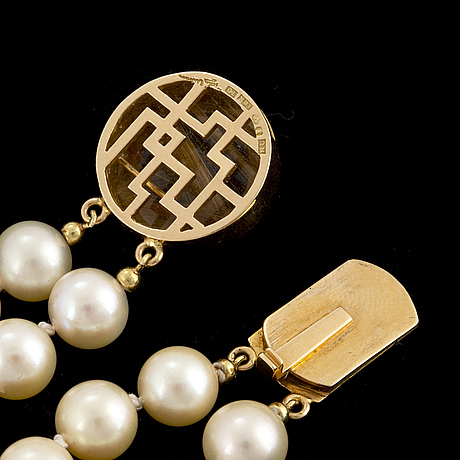 A two strand cultured pearl necklace with a rey urban clasp in 18k gold set with rutilated quartz.