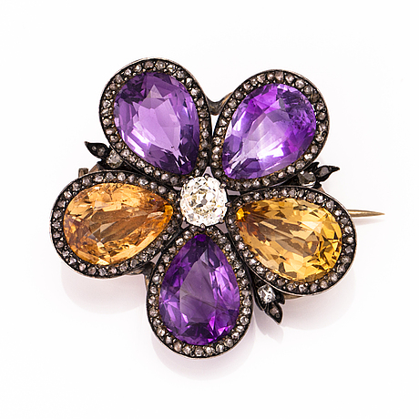 A silver and gold brooch with three amethysts, two citrines, one old cut diamond ca 0.7 ct and rose cut diamonds.