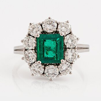 967. An 18K white gold ring set with a faceted emerald ca 1.15 cts and round brilliant-cut diamonds.