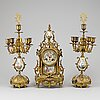 A table clock and a pair of candelabra, probably france. ca 1900.
