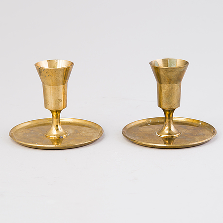 A pair of pierre forsell candle sticks produced by skultuna mässingsbruk, sweden.