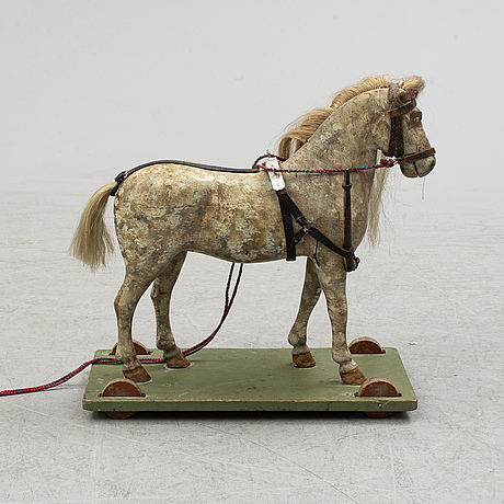 A painted early 20th century toy horse on wheels.
