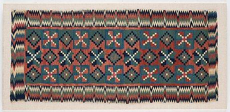 """A carriage cushion, double-interlocked tapestry, """"Åttabladsstjärnor"""", ca 46,5 x 104 cm, scania (sweden) around 1800."""
