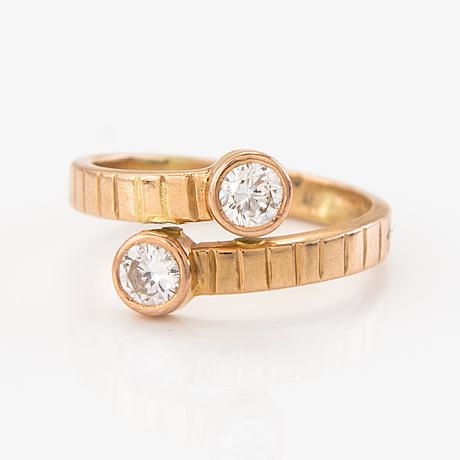 Brilliant-cut diamond crossover ring.