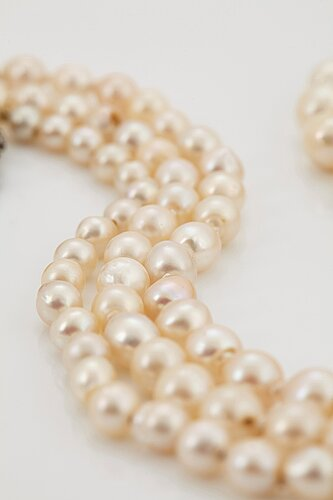A three strand cultured pearl necklace with a clasp in 18k gold and silver set with rose- and old-cut diamonds.