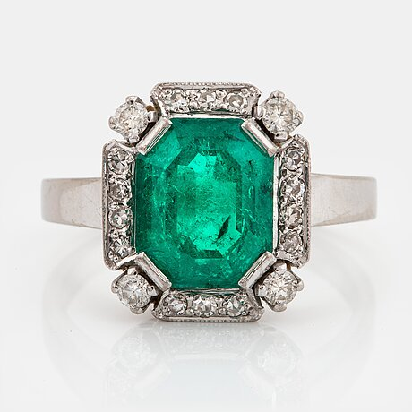 An 18k white gold ring set with a faceted emerald and round brilliant-cut diamonds.