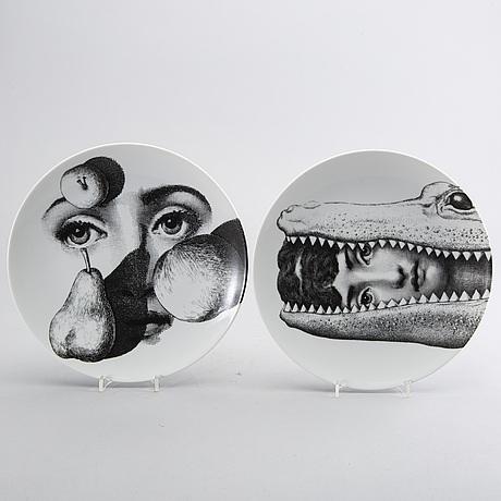 Piero fornasetti, a set of two porcelain plates.