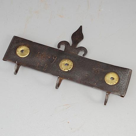 An iron wall hanger, dated 1809.