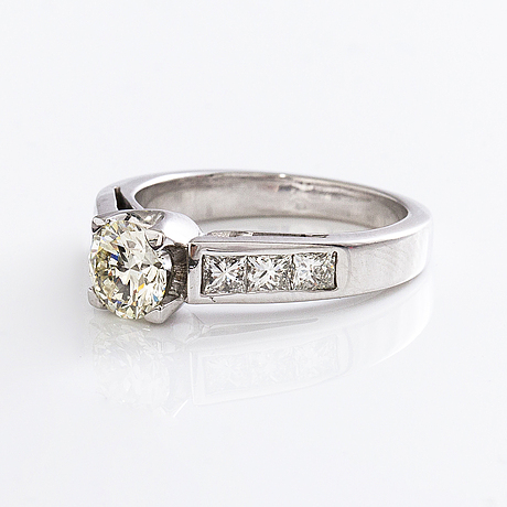 An 18k gold ring with a brilliant-cut diamond ca. 1 ct and princess-cut diamonds ca. 0.7 ct in total.