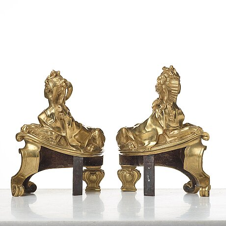 A pair of french 19th century fire dogs, after design of the sphinxes attributed nicolas coustou 1658-1733.