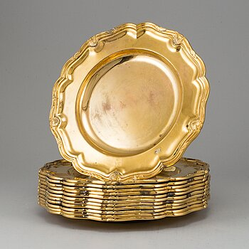 A German set of twelve 19th century silver-gilt plates, mark of Hossauer, Berlin. Rokoko-style.