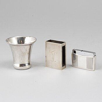 A silver vodkacup, lighter and matchholder.