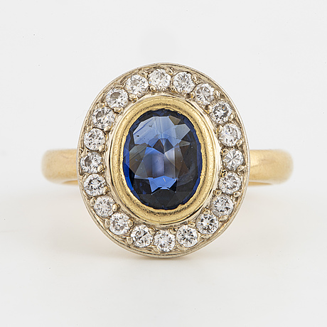 An oval faceted sapphire and brilliant-cut diamond cluster ring.