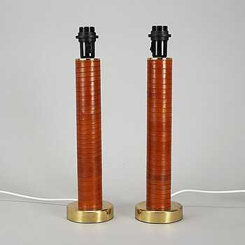 A pair of brass and leather table lamps.