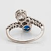 A platinum ring set with old-cut diamonds and a faceted sapphire.