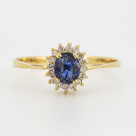 Oval mixed-cut sapphire and round brilliant-cut diamond halo ring.