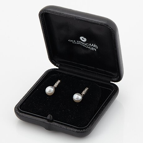 A pair of 18k white gold earrings set with drop formed pearls and eight-cut diamonds.