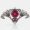 A silver and 14k gold brooch set with a faceted pink tourmaline and old- and rose-cut diamonds.