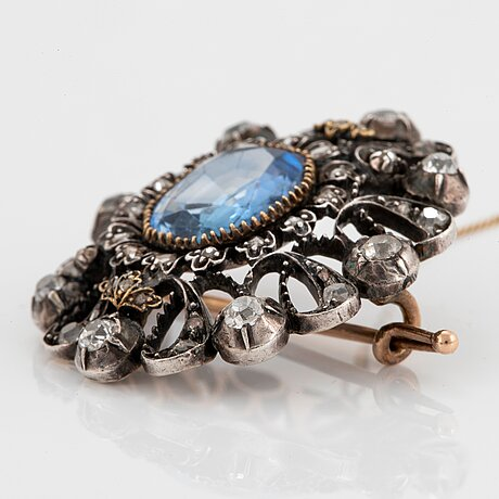 A 14k gold and silver brooch set with a synthetic sapphire and old- and rose-cut diamonds.