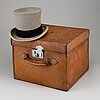 A leather hat box and top hat from scott's hatters, london, england, early 20th century.