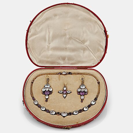 A demi parure comprising a necklace, a pair of earrings and a pendant.