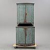 An early 19th century painted corner cabinet.
