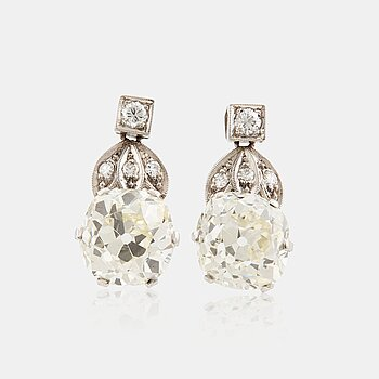 873. A pair of platinum earrings set with cushion formed old-cut diamonds with a total weight of ca 6.00 cts quality ca L/M v.
