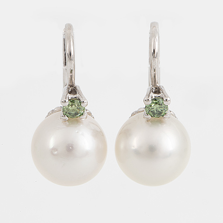 A pair of cultured south sea pearl and color treated green diamond earrings.