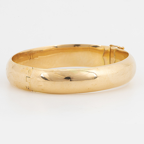 An 18k gold bangle.