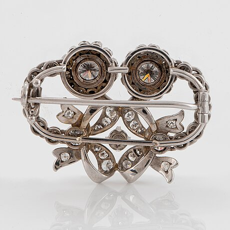 An 18k white gold brooch set with round brilliant- and eight-cut diamonds.