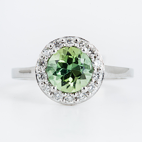 An round faceted green tourmaline and brilliant-cut diamond ring.