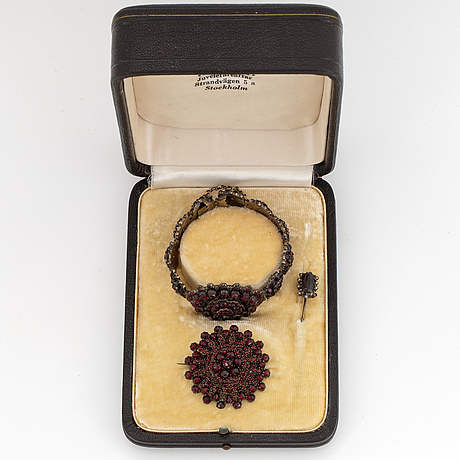 A bracelet and two brooches with faceted garnets.