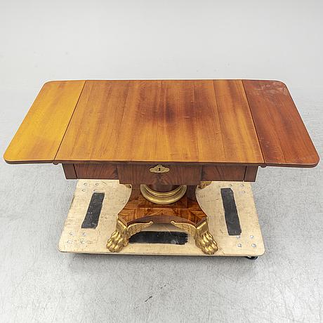 A mahogany veneered empire style table, early 20th century.