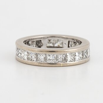 An 18K white gold eternity ring set with princess-cut diamonds.