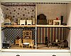 A 20th century cabinet/ doll's house with furniture and dolls.