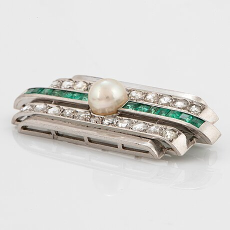A platinum brooch set with old- and rose-cut diamonds, faceted emeralds and a pearl.