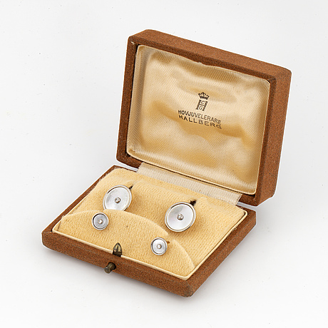 A pair of cufflinks and a pair of shirt buttons.