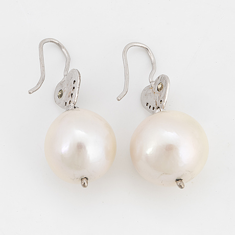 Cultured white freshwater pearl and brilliant-cut diamond earrings.