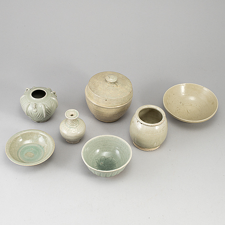 A group of seven pale olive green south east asian ceramics, songstyle, 20th century.