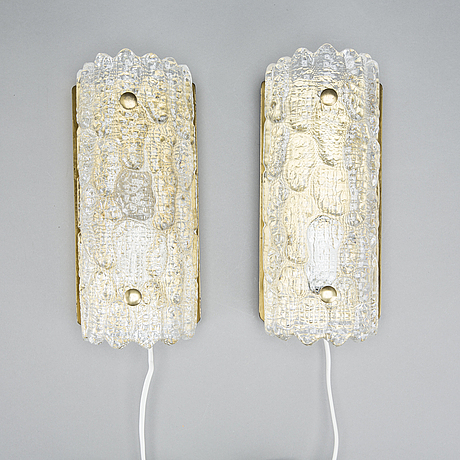 Carl fagerlund, a pair of glass and brass orrefors wall lamps.