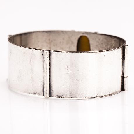 A silver bracelet with a tiger's eye. h. kaksonen oy, helsinki 1956.