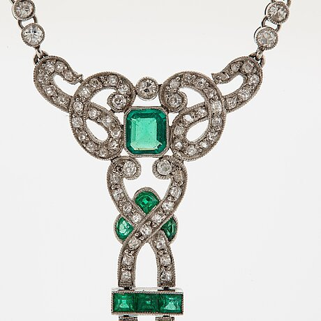 A platinum necklace set with faceted emeralds and old- and eight-cut diamonds.
