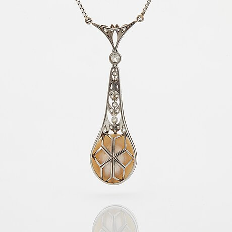 A platinum pendant set with a half pearl and old-cut diamonds.