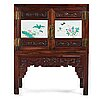 A chinese wooden cabinet with two porcelain placques, early 20th century.