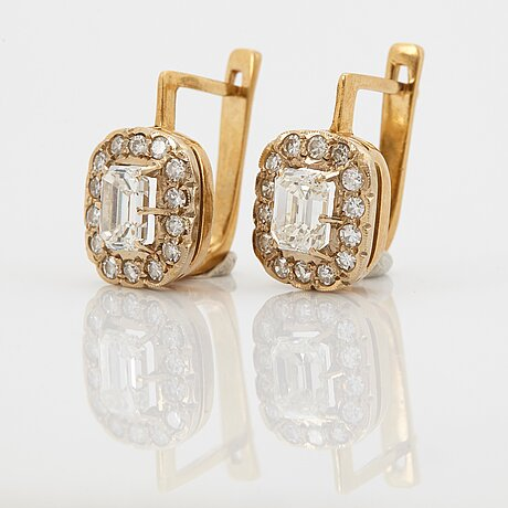 A pair of earrings in 18k gold set with emerald-cut diamonds.